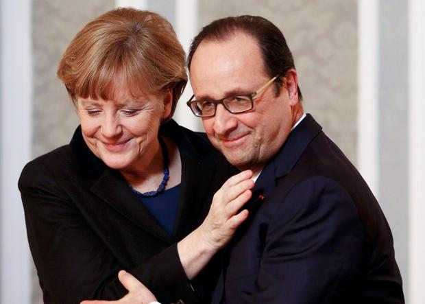 German Chancellor Angela Merkel (L) embraces French President Francois Hollande during a meeting with the media after peace talks on resolving the Ukrainian crisis in Minsk