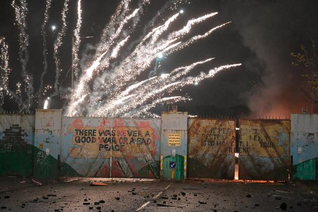 BELFAST, NORTHERN IRELAND - APRIL 07: Fireworks explode as youths exchange projectiles through the Peace Gate during clashes at the Springfield Road/Lanark Way interface on April 7, 2021 in Belfast, Northern Ireland. Violence broke out after a Loyalist protest, with youths attacking police officers and petrol-bombing a bus. (Photo by Charles McQuillan/Getty Images)