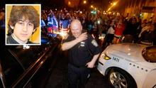 A police officer reacts to news of the arrest of one of the Boston Marathon bombing suspects. Photo: AP