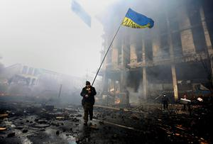 An anti-government protester holds a Ukranian flag as he advances through burning barricades in Kiev's Independence Square