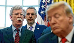 Tuning in: Donald Trump listens to his national security adviser John Bolton. Photo: Leah Millis/Reuters