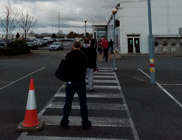 Customers social distancing in the queue to enter a Tesco store in New Ross, Co Wexford. The Covid-19 pandemic is disrupting businesses around the globe. Photo:PA Wire