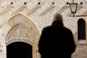 A man walks towards the main entrance of the Monte dei Paschi bank headquarters in Siena.