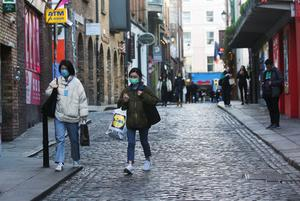 Women stroll through Temple Bar after pubs decided to close. Photo: Reuters/Lorraine O'Sullivan