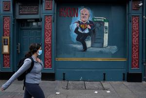 A woman wearing a face mask walks past a mural depicting Dr Tony Holohan in Dublin yesterday. Photo: REUTERS