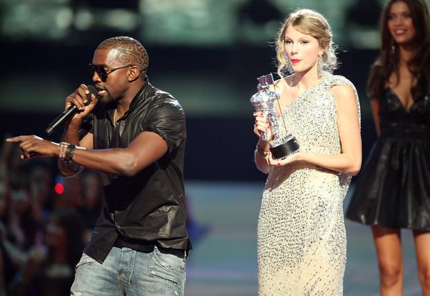 Kanye West (L) jumps onstage after Taylor Swift (C) won the