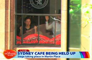 This image taken from video shows people holding up hands inside a cafe in Sydney, Australia Monday (AP Photo/Channel 7 vide AP Video) AUSTRALIA OUT