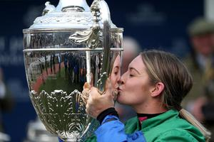 Sealed with a kiss: Maxine O'Sullivan celebrates with the trophy after winning the Foxhunter Chase aboard 66/1 shot It Came To Pass, trained by her father Eugene O'Sullivan, at Cheltenham yesterday. Photo: Reuters