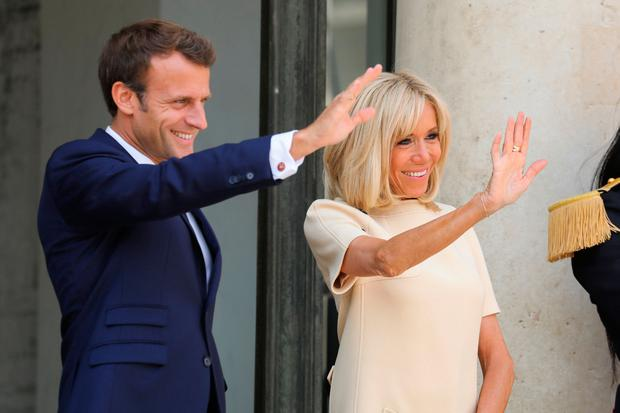French President Emmanuel Macron (L) and his wife Brigitte Macron wave goodbye to Ecuador's President and his wife after a meeting at the Elysee Palace on July 11, 2019, in Paris. (Photo by Ludovic MARIN / AFP)