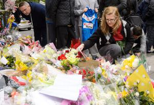 Ingrid Loyau-Kennett, who was praised for her bravery in calmly talking to one of the attackers as he stood clutching a knife with bloodied hands, looks at the floral tributes outside the Royal Artillery Barracks, in Woolwich, east London