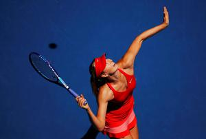 Maria Sharapova of Russia serves to compatriot Ekaterina Makarova during their women's singles semi-final match