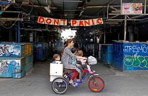 A woman rides a bicycle with her children past a banner hanging at the entrance of Shuk HaCarmel (Caramel) market in the Israeli coastal city of Tel Aviv  (Photo by JACK GUEZ / AFP) (Photo by JACK GUEZ/AFP via Getty Images)
