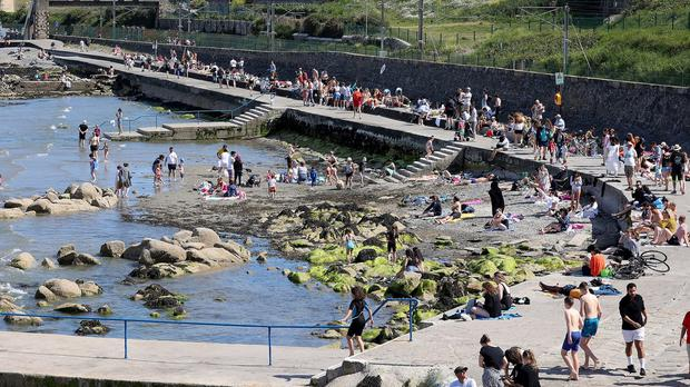 Crowds enjoying the warm weather at Seapoint in Dublin yesterday. Photo: Frank McGrath
