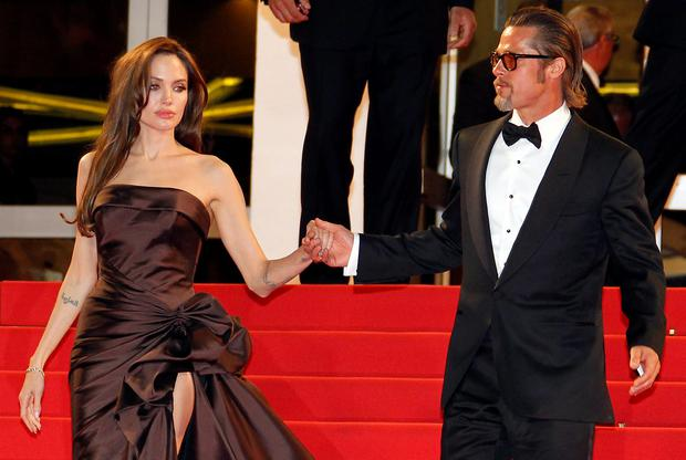 US actor Brad Pitt and US actress Angelina Jolie leave the red carpet after the screening of