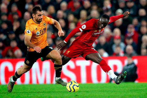 Wolverhampton Wanderers' Jonny (left) and Liverpool's Sadio Mane battle for the ball during the Premier League match at Anfield Stadium, Liverpool.