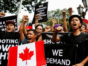 Protesters chant slogans demanding justice for the victims of Malaysia Airlines Flight MH17 as they follow the lead of organisers of a rally held by UMNO's youth wing outside the Russian embassy in Kuala Lumpur