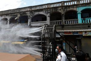 Firefighters spray disinfectant along a street during Gujarat's government-imposed lockdown as a preventive measure against coronavirus, in Ahmedabad  (Photo by SAM PANTHAKY/AFP via Getty Images)