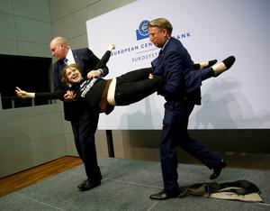 Security officers detain a protester who jumped on the table in front of the European Central Bank President Mario Draghi during a news conference in Frankfurt, April 15, 2015. REUTERS/Kai Pfaffenbach