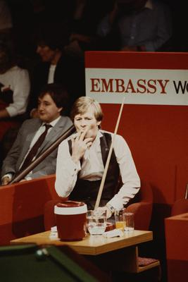 Different cloth: Alex Higgins smoking a cigarette during his 1983 World Championship semi-final defeat to rival Steve Davis. Photo by Adrian Murrell/Getty Images
