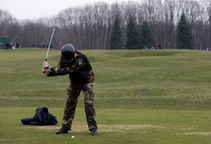 A man plays golf as anti-government protesters walk on the grounds of the Mezhyhirya residence of Ukraine's President Viktor Yanukovich