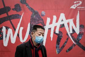 January: A man wears a mask while walking in the street in Wuhan. Photo: Getty Images