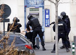 """A man, who had taken two hostages in a post office, is arrested by French Research and Intervention Brigades (BRI) police officers in Colombes, outside Paris. Police sources said several post office clients had managed to escape and that the gunman himself had called them. The sources said he was """"speaking incoherently"""" and was heavily armed with grenades and Kalashnikovs."""