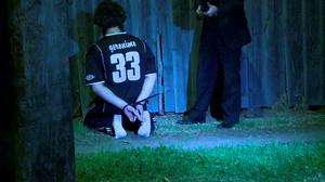 A man detained by police during a raid kneels on the ground in Sydney