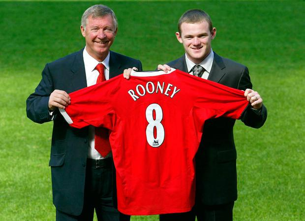 Wayne Rooney signing for Manchester United with former manager Sir Alex Ferguson. Photo: Gareth Copley/PA Wire