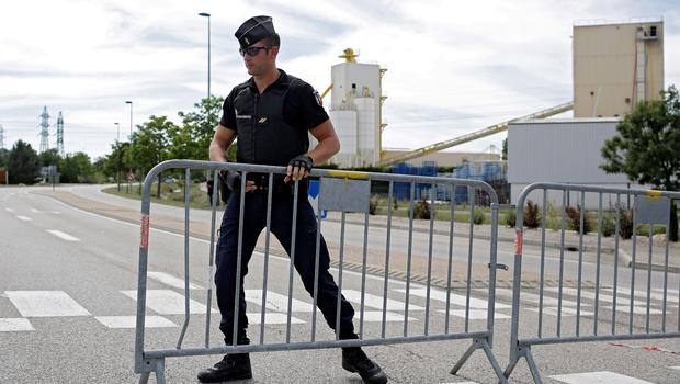 A police officer blocks the road leading to a plant where an attack took place, Friday, June 26, 2015 in Saint-Quentin-Fallavier, southeast of Lyon, France.  A man with suspected ties to French Islamic radicals rammed a car Friday into an American gas factory in southeastern France, triggering an explosion that injured two people, officials said. The severed head of a local businessman was left hanging at the factory's entrance, along with banners with Arabic inscriptions, they said. (AP Photo/Laurent Cipriani)