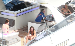 Former Formula One star Eddie Irvine with three bikini-clad women on his yacht. Photo credit: Splash News / Corbis Images
