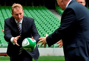 Taoiseach Enda Kenny passes a rugby ball to Michael Ring, Minister of State at the Department of Transport, Tourism and Sport, at the Rugby World Cup 2023 Oversight Board meeting in the Aviva Stadium in Dublin.