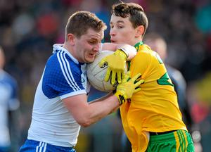 Monaghan's Dermot Malone breaks through a challenge from Eoin McHugh, Donegal