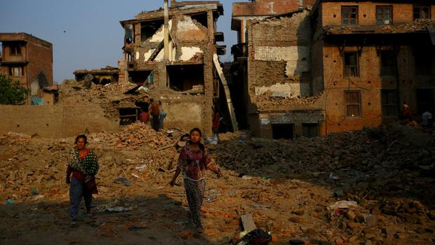People walk in front of the wreckage of collapsed houses after the April 25 earthquake in Bhaktapur, Nepal, June 5, 2015. REUTERS/Navesh Chitrakar