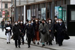 Tourists wearing protective masks walk near Duomo square, as a coronavirus outbreak continues to grow in northern Italy, in Milan, Italy, February 27, 2020. REUTERS/Yara Nardi