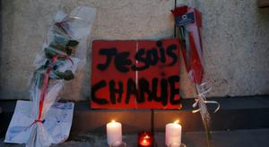 """Flowers, candles and a placard which reads """"I am Charlie"""" are displayed to pay tribute during a gathering at the Place de la Republique in Paris, following a shooting by gunmen at the offices of weekly satirical magazine Charlie Hebdo. Reuters/Gonzalo Fuentes"""