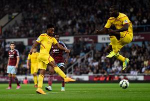 Raheem Sterling scores for Liverpool as teammate Mario Balotelli jumps to avoid the shot during the Premier League match against West Ham United at Upton Park. Photo: Mike Hewitt/Getty Images