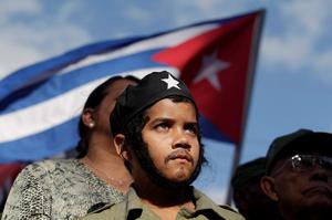 "Brian Gracia, 11, dressed as revolutionary leader Ernesto 'Che' Guevara, watches a convoy of military trucks, re-enacting the triumphal 1959 march into Havana by Fidel Castro and his ""Barbudos"" (bearded) guerrillas, in Havana REUTERS/Stringer"