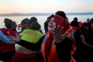A Syrian woman reacts as she arrives aboard a dinghy after crossing from Turkey, to the island of Lesbos, Greece, on Saturday, Sept. 19, 2015.  (AP Photo/Petros Giannakouris)