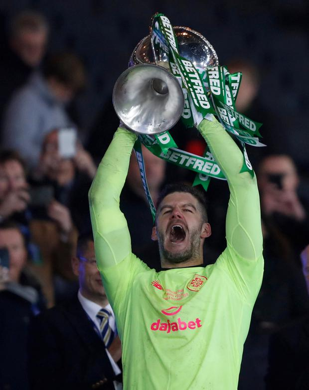 Fraser Forster celebrates Celtic's win by lifting the trophy. Pic: Reuters