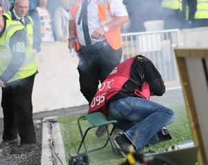Photographer Darren Kidd is injured after a firecracker explodes under his seat during the Euro 2016 Qualifier at Windsor Park in Belfast on Saturday