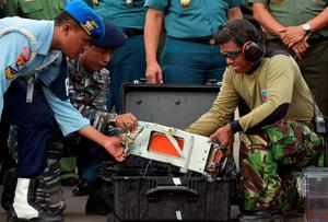 The flight data recorder of AirAsia QZ8501 is lifted out of a carrying case in Indonesia