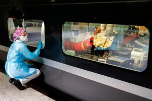 Mercy mission: A medical worker watches from a platform of the Gare d'Austerlitz train station through the window of a medicalised TGV high-speed train before its departure to evacuate patients infected with Covid-19 from Paris to other hospitals in western France. Photo: AFP via Getty Images