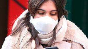 Covered up: A pedestrian in London wears a protective face mask. Photo: PA