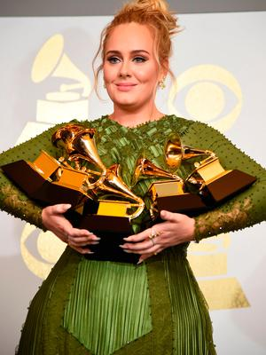 """Adele poses in the press room with her trophies, including the top two Grammys of Album and Record of the Year for her blockbuster hit """"Hello"""" and the album """"25"""", during the 59th Annual Grammy music Awards"""