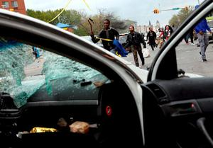Demonstrators run by a damaged Baltimore police vehicle during clashes in Baltimore, Maryland.  Photo: Reuters