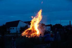 People gather to watch a bonfire on Belfast's Shankill Road as bonfires were set to be lit at midnight, as part of a loyalist tradition to mark the anniversary of the Protestant King William's victory over the Catholic King James at the Battle of the Boyne in 1690. Photo credit: Niall Carson/PA Wire