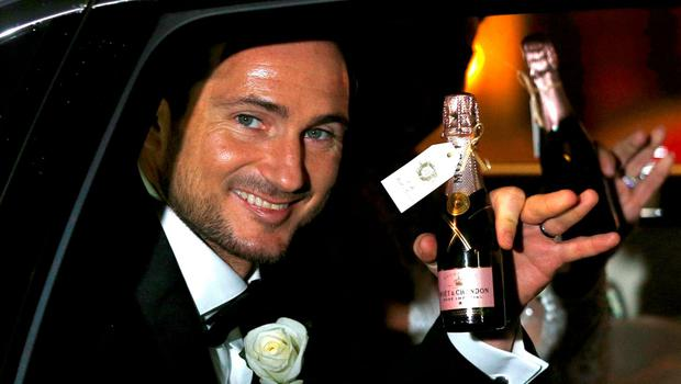 Former Chelsea and England soccer player Frank Lampard waves a miniature bottle of champagne as he and his wife, British TV personality Christine Bleakley, leave church after they married in London, Britain, December 20, 2015