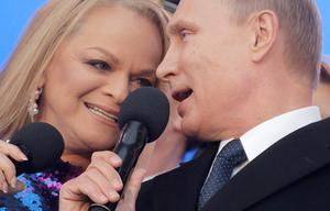 Russia's President Vladimir Putin (R) and Russian pop singer Larisa Dolina sing the Russian national anthem