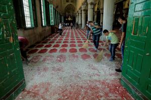 Palestinians sweep up rock debris on the carpet in Al Aqsa mosque after clashes with Israeli police on the compound known to Muslims as Noble Sanctuary and to Jews as Temple Mount in Jerusalem's Old City REUTERS/Ammar Awad