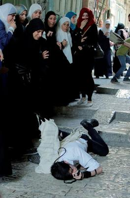 Palestinian women look on as an Orthodox Jew lays on the floor after he was attacked by other Palestinians during clashes in Jerusalem's Old City